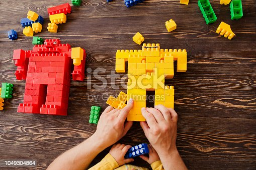 544818734 istock photo Father and child playing with lots of colorful plastic blocks constructor on a table 1049304864