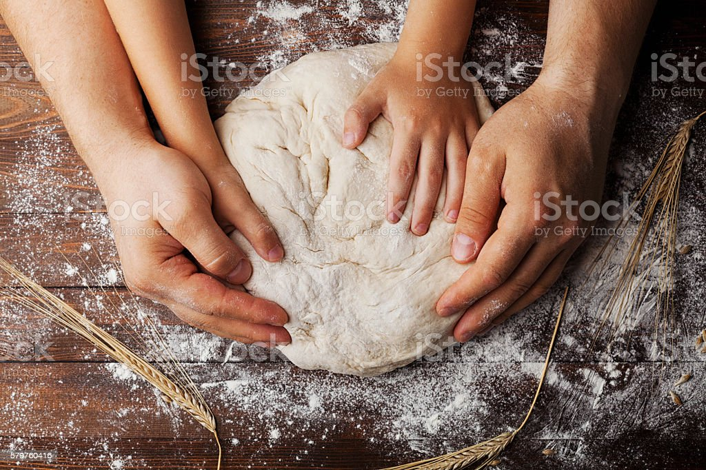 Father and child prepares dough with flour and wheat ears Father and child hands prepares the dough with flour, rolling pin and wheat ears on rustic wooden table from above. Homemade pastry for bread or pizza. Bakery background. Adult Stock Photo