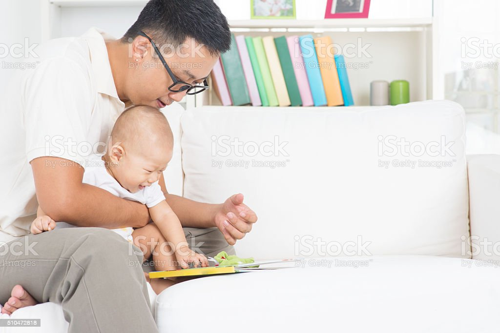 Father and child reading story book stock photo