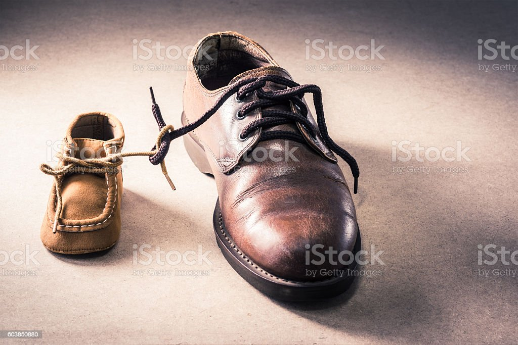 father and child shoes on grunge background stock photo