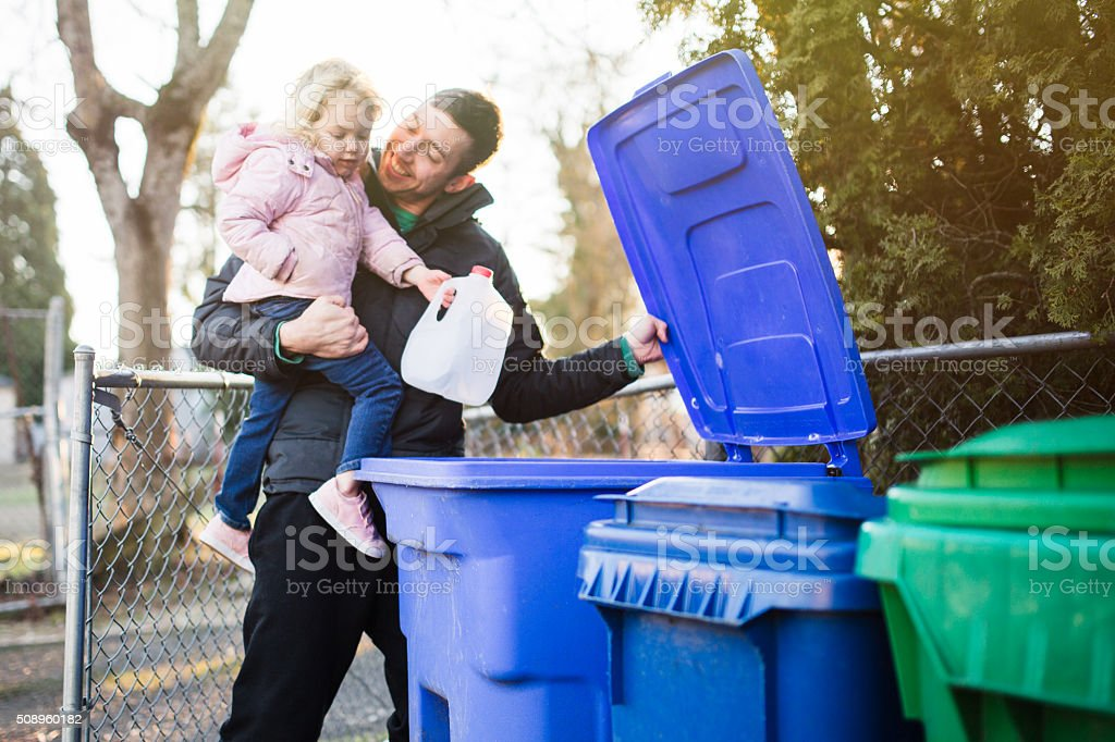 Father and Child Taking Out Recycle Trash stock photo