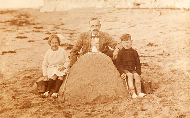 Father and Children at Beach Vintage sepia photograph of a father and his children by a large sandcastle at the beach in 1920's. Some dust and scratches that reflect age of image. edwardian style stock pictures, royalty-free photos & images