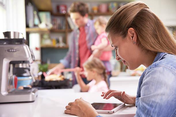 padre prepara comida familiar mientras madre uso tableta digital - padre que se queda en casa fotografías e imágenes de stock