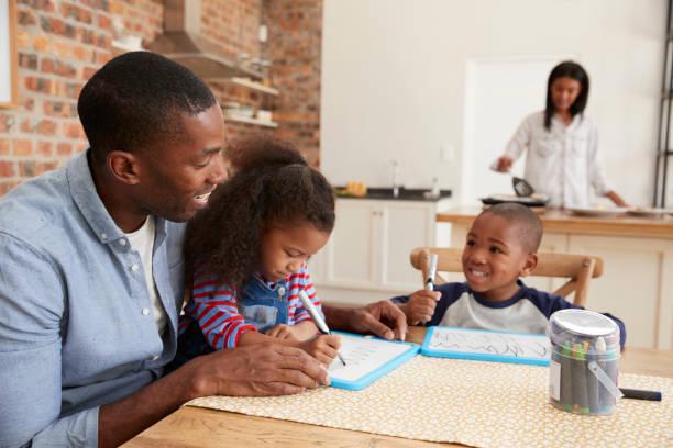 vater und kinder zeichnen am tisch, als mutter mahlzeit bereitet - kochkunst stock-fotos und bilder