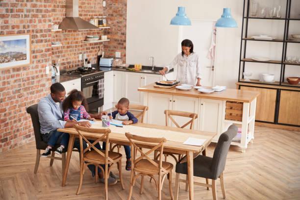 vader en kinderen tekenen aan tafel als moeder zich maaltijd voorbereidt - groothoek stockfoto's en -beelden