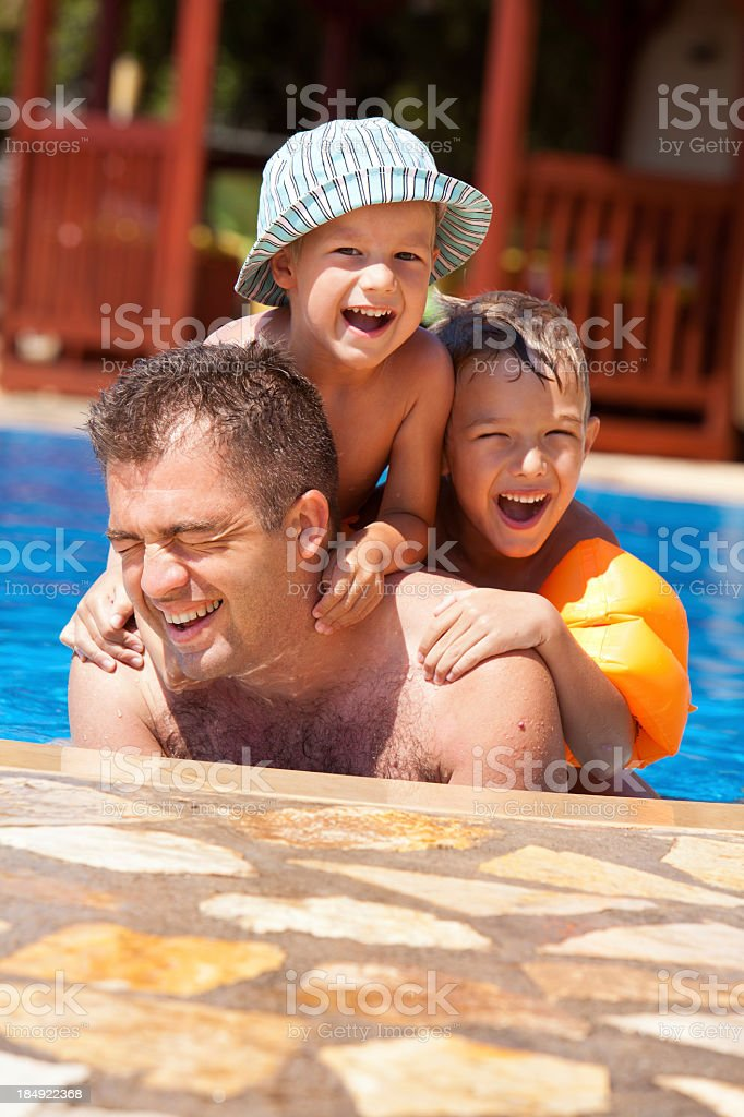 Father and children enjoying in the swimming pool royalty-free stock photo