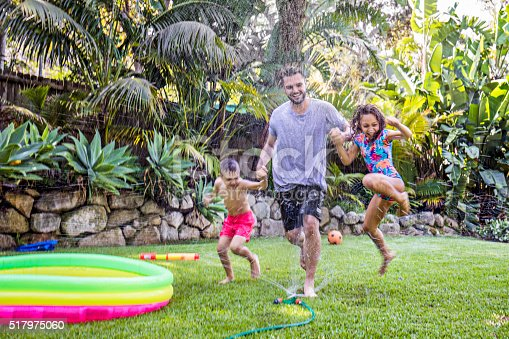 Father and children jumping in sprinkler in the backyard garden.