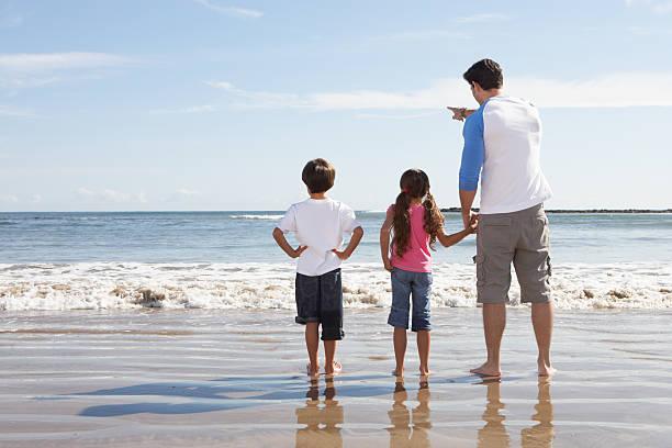 Vater und Kinder, Blick auf das Meer vom Strand – Foto