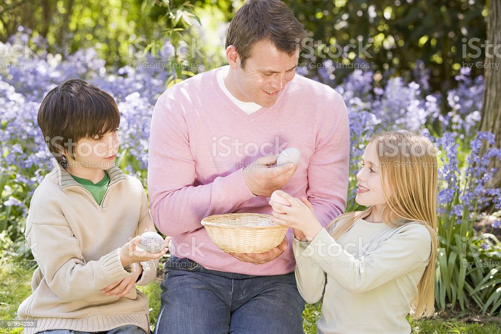 Father and children on Easter looking for eggs outdoors royalty-free stock photo