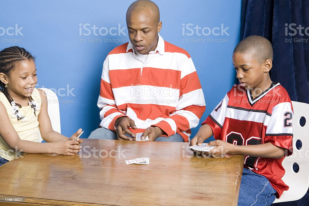 Father and children playing cards stock photo