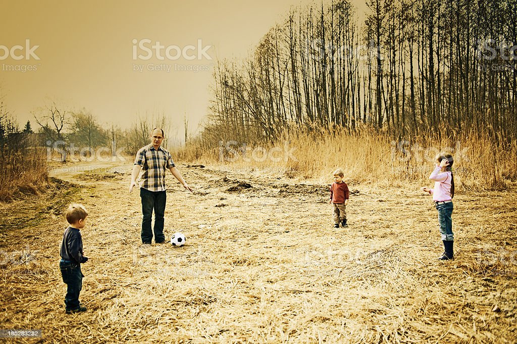 Father and children playing football royalty-free stock photo