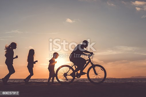 586180632 istock photo Father and children playing on the beach at the sunset. 606237912