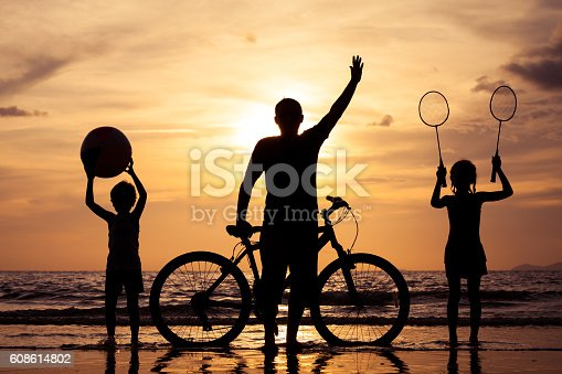 586180632istockphoto Father and children playing on the beach at the sunset. 608614802