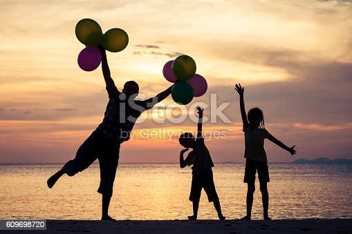 586180632istockphoto Father and children playing on the beach at the sunset. 609698720