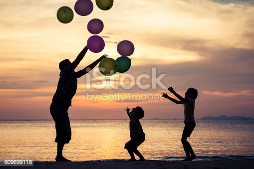 586180632istockphoto Father and children playing on the beach at the sunset. 609699118