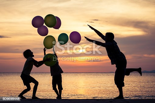 586180632istockphoto Father and children playing on the beach at the sunset. 609699448