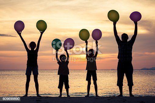 586180632istockphoto Father and children playing on the beach at the sunset. 609699890