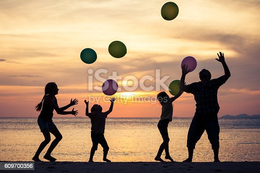 586180632istockphoto Father and children playing on the beach at the sunset. 609700356