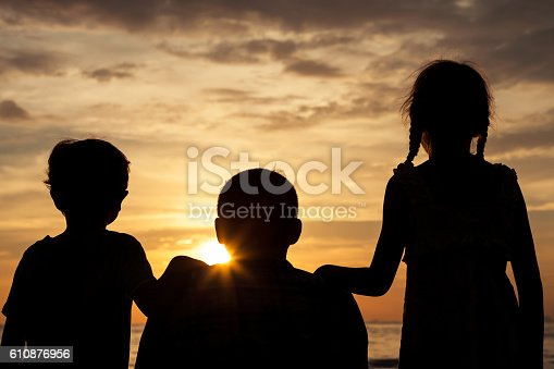 586180632istockphoto Father and children playing on the beach at the sunset. 610876956