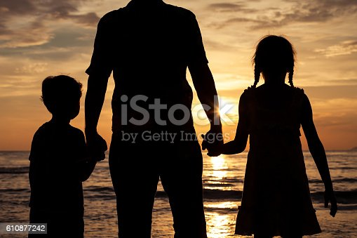 586180632istockphoto Father and children playing on the beach at the sunset. 610877242
