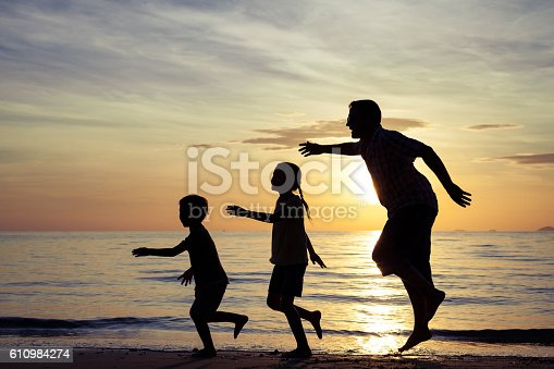 586180632istockphoto Father and children playing on the beach at the sunset. 610984274
