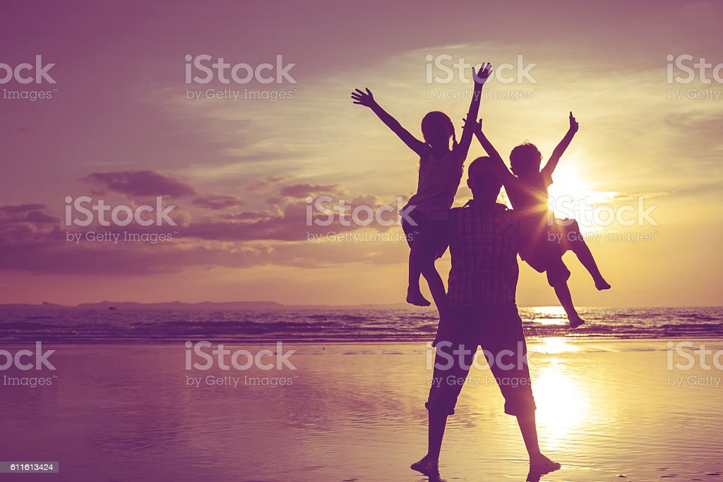 Father and children playing on the beach at the sunset. royalty-free stock photo