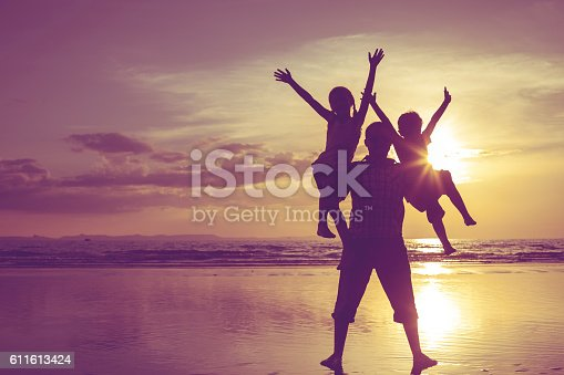 586180632istockphoto Father and children playing on the beach at the sunset. 611613424