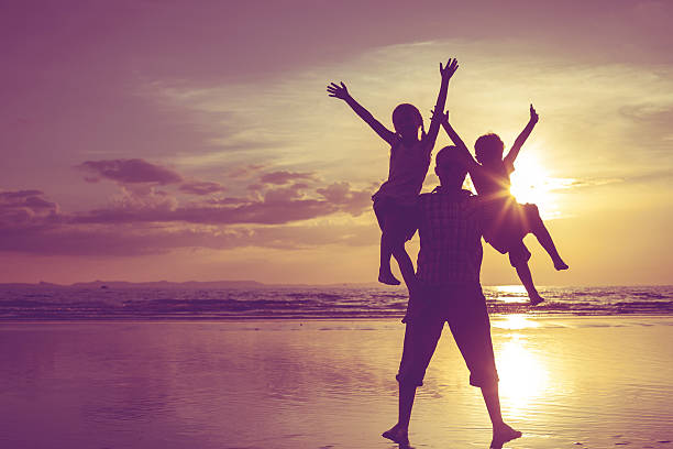 Father and children playing on the beach at the sunset. stock photo