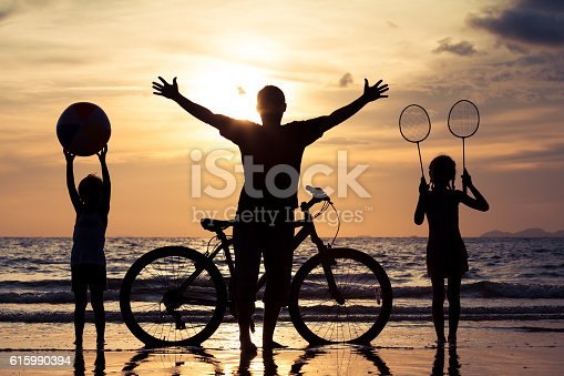 586180632istockphoto Father and children playing on the beach at the sunset. 615990394