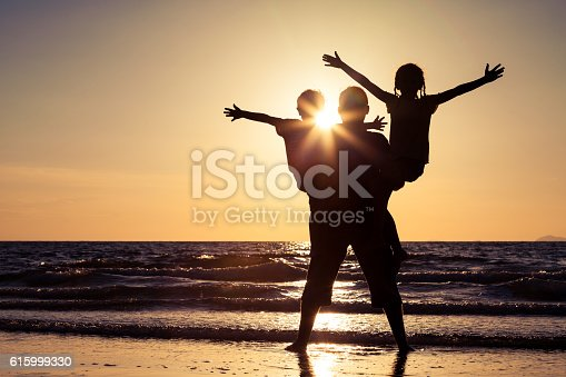 586180632istockphoto Father and children playing on the beach at the sunset. 615999330