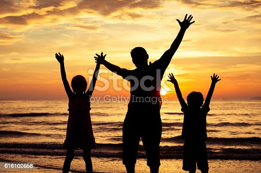 586180632istockphoto Father and children playing on the beach at the sunset. 616102658