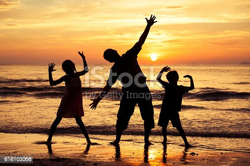 586180632istockphoto Father and children playing on the beach at the sunset. 616103058