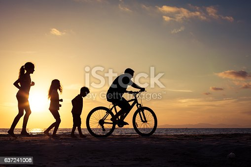 586180632 istock photo Father and children playing on the beach at the sunset. 637241008