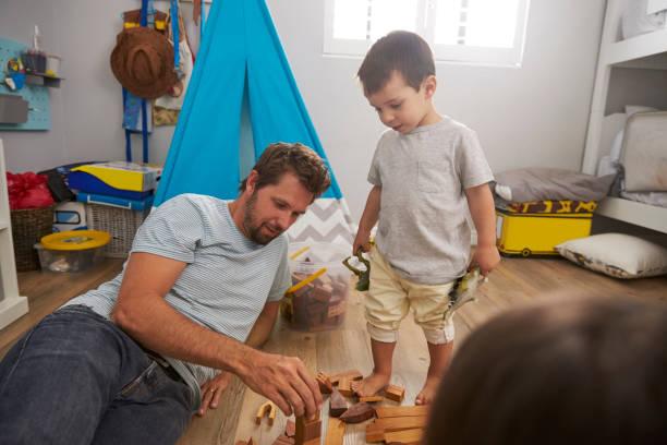 vater und die kinder spielen mit bausteinen im schlafzimmer - tipi bett stock-fotos und bilder