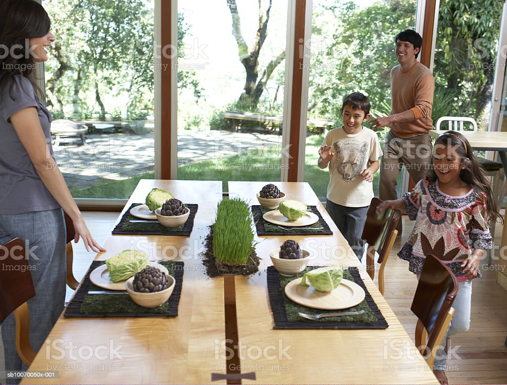 Father and children (6-11) running toward dining table, cheering royalty-free stock photo