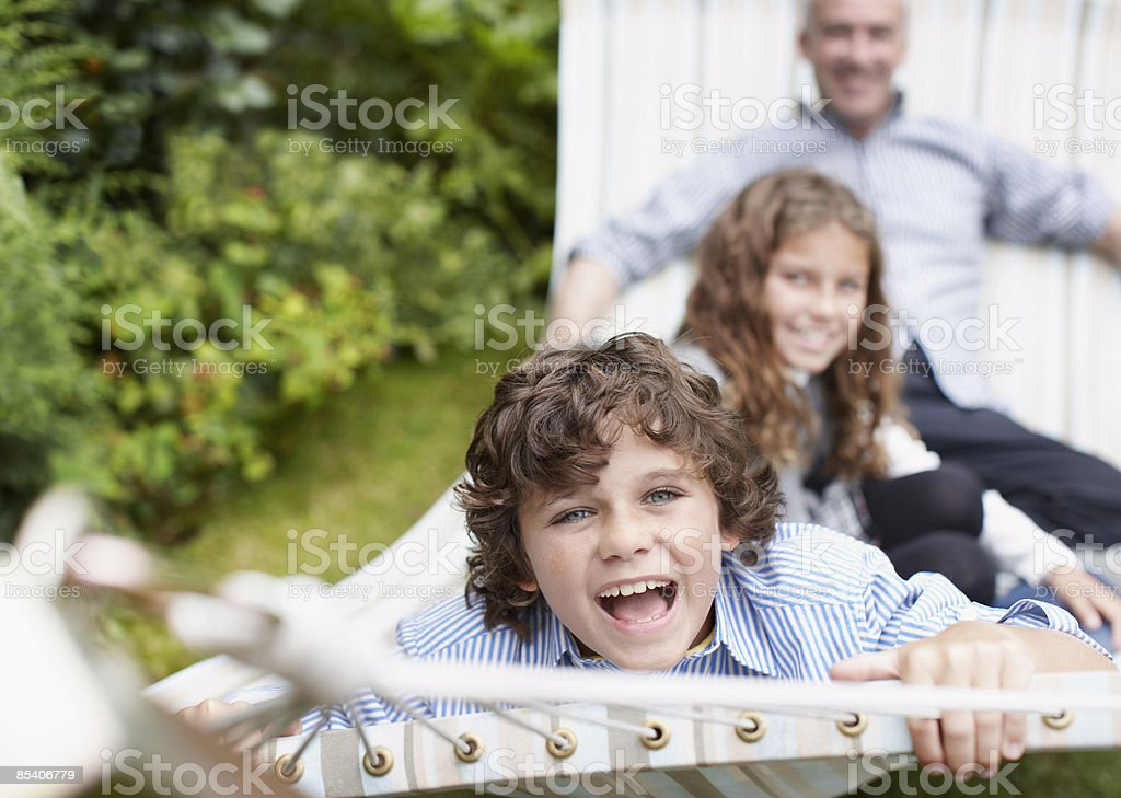 Father and children sitting in hammock royalty-free stock photo