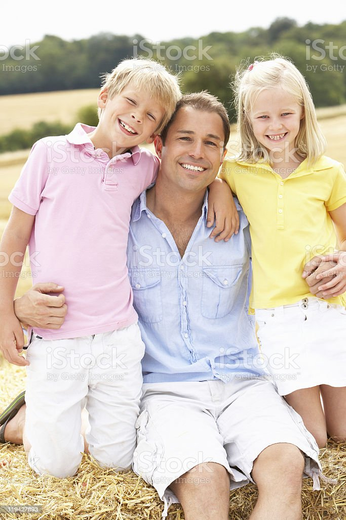 Father And Children Sitting On Straw Bales In Harvested Field royalty-free stock photo