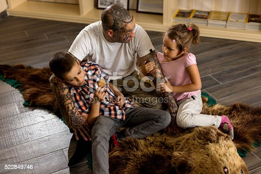 Young father sitting on bearskin rug with his son and daughter and talking.