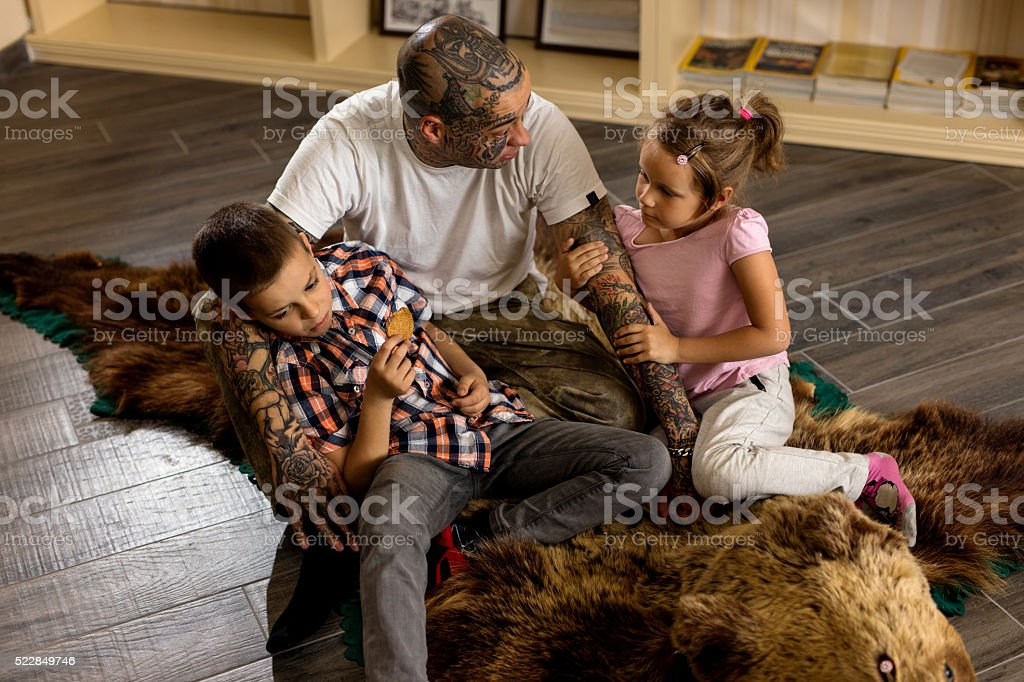 Father and children sitting on the carpet and communicating. stock photo