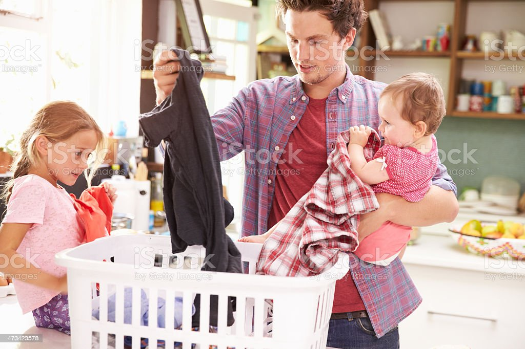 Father And Children Sorting Laundry In Kitchen Father And Children Sorting Laundry In Kitchen 20-29 Years Stock Photo
