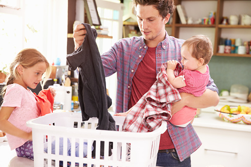 Father And Children Sorting Laundry In Kitchen Stock Photo - Download Image Now