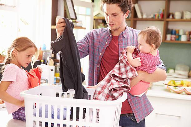 padre de niños y lavandería y de clasificación en la cocina - padre que se queda en casa fotografías e imágenes de stock