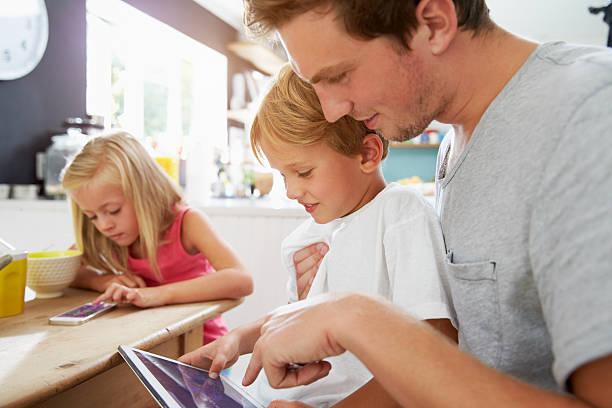 padres e hijos usando dispositivos digitales en mesa de desayuno - padre que se queda en casa fotografías e imágenes de stock