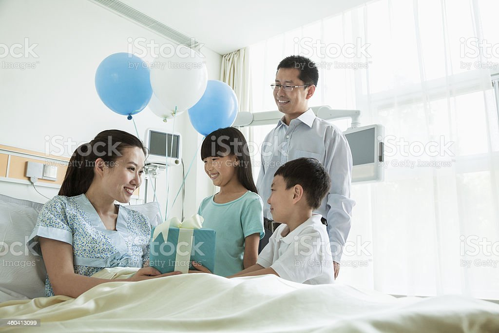 Father and children visiting their mother in the hospital stock photo