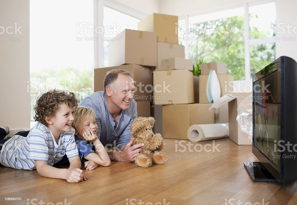 Father and children watching television in new house stock photo