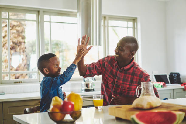 Father and cute little son high fiving together at home stock photo