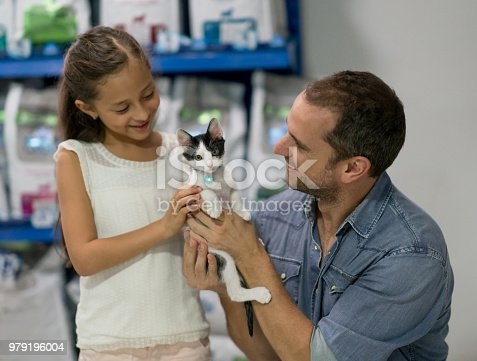 Portrait of a happy father and daughter adopting a little cat at a rescue house – animal concepts