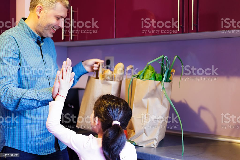 Father and daughter after shopping groceries in supermarket stock photo