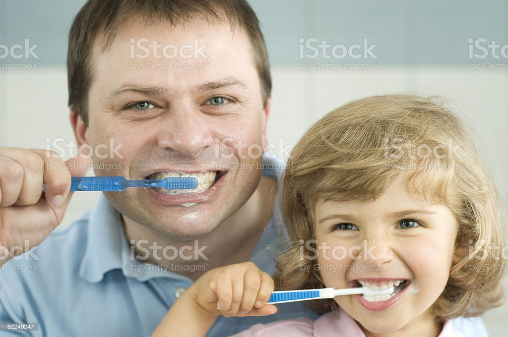 A father and daughter are brushing their teeth royalty-free stock photo