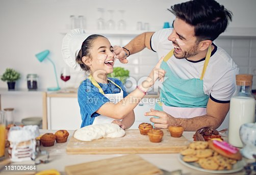 Father and daughter are cooking together in the kitchen